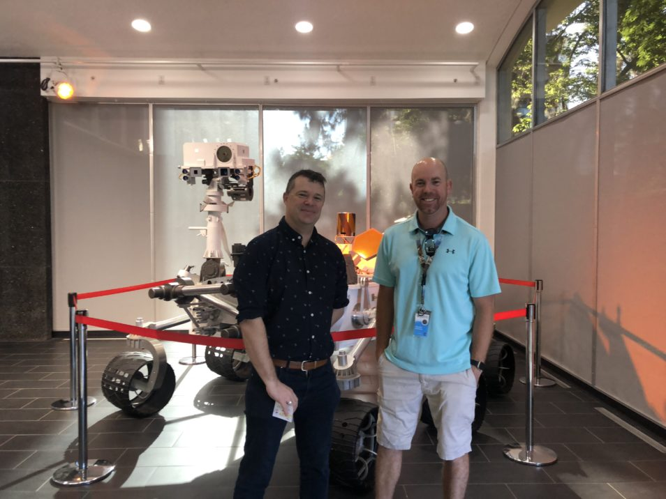 two men stand smiling in front of a robotic vehicle, cordoned off by red tape, in a small office foyer.
