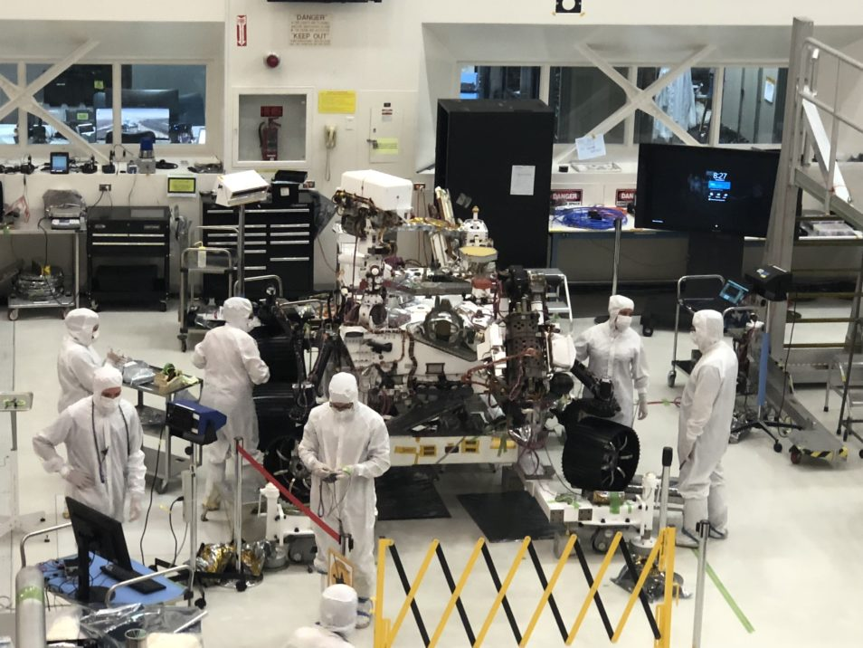a team of six researchers in hooded white coveralls, including face masks, work on a large piece of technology, in a high tech lab.