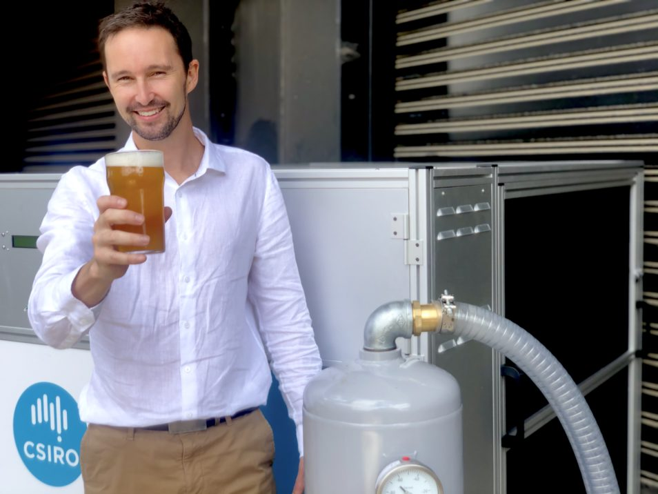 Man holding beer in front of CO2 Capture Machine