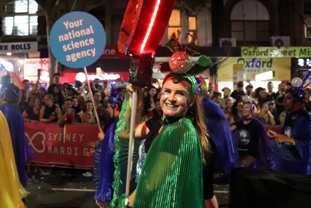 Woman in glittery green face paint and green cape and feathers holding up a sign. She is smiling to the camera.