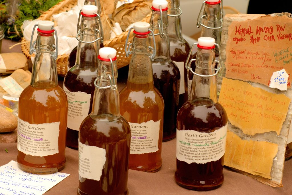Bottles of dark amber coloured liquid with labels saying they're apple cider vinegar