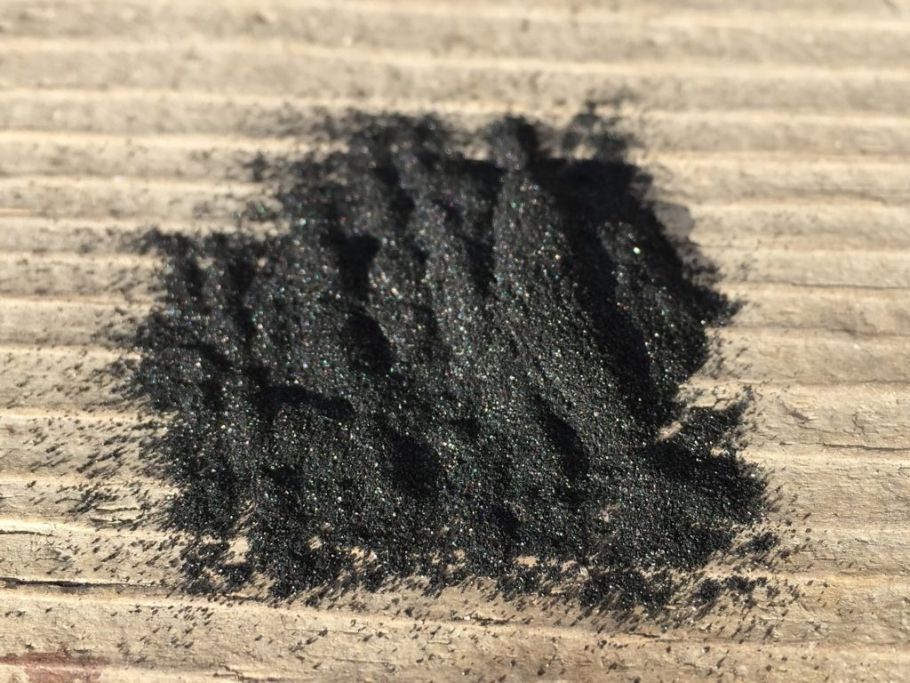 A pile of charcoal powder on a beige background.