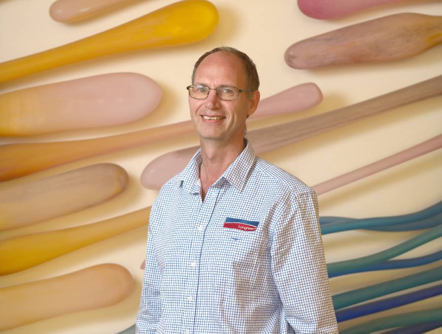 Man with glasses standing in front of a wall with colourful patterns on it