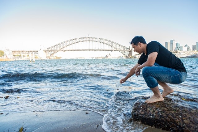 Man squatting down to collect water sample in front of Sydney Harbour Bridge