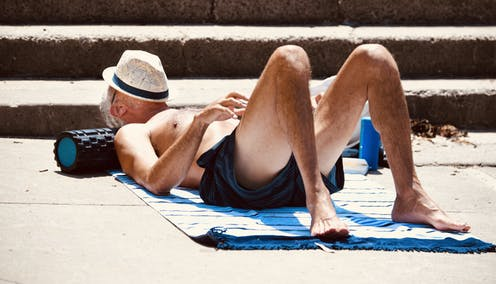 man lying on a towel with a hat over his face