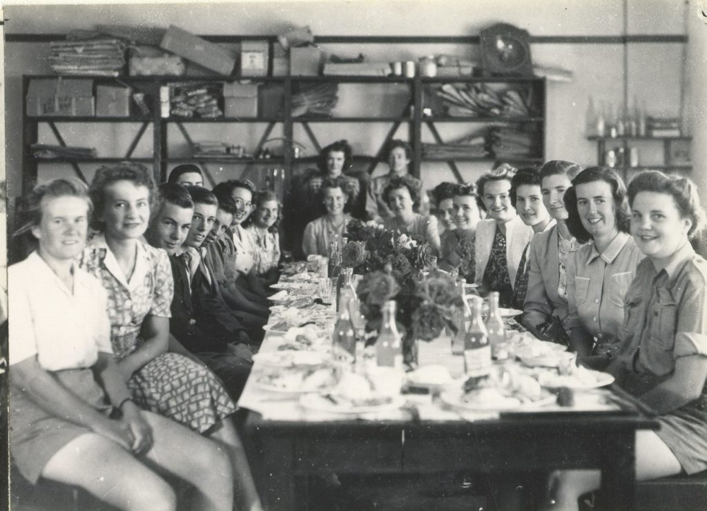 a black and white photo of a group of women sitting around a table. they are some of the first female scientists australia
