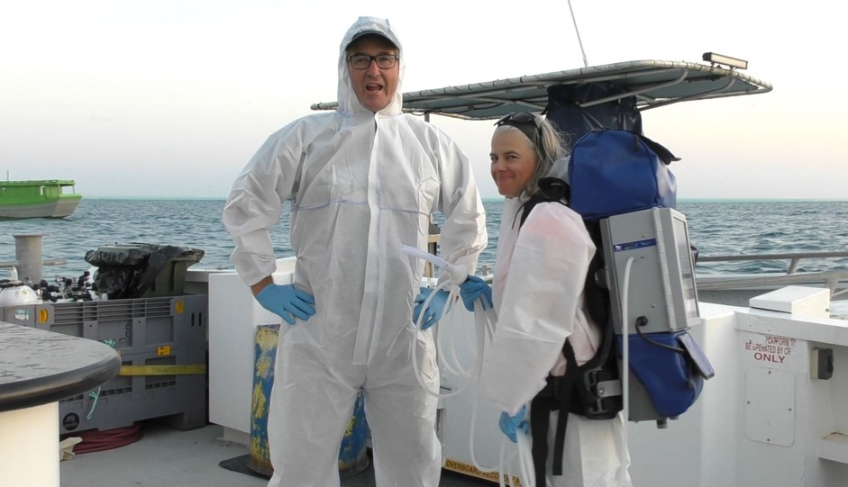 Image shows a man and a woman standing on the back of a boat wearing white body suits. The woman is wearing a technical contracption similar to that seen in the move 'Ghostbusters'. Scientists are studying fish species.