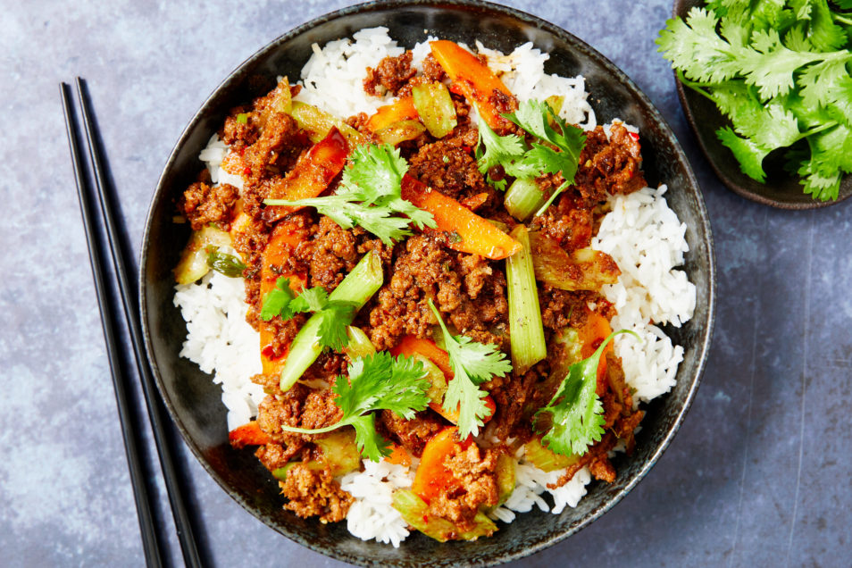 Spicy plant-based mince with chilli and ginger in black bowl on white rice