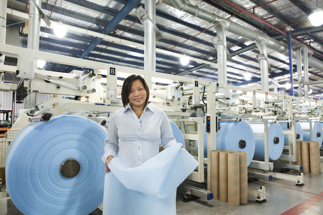 person in factory at Textor Technologies production facility with moisture-trapping fabric co-developed with CSIRO. Rolls of fabric in background.