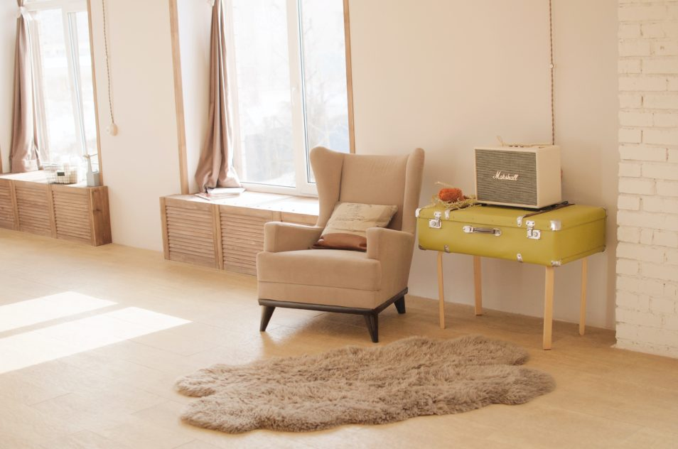 Loungeroom with armchair, sheepskin and curtains open with sun coming in window