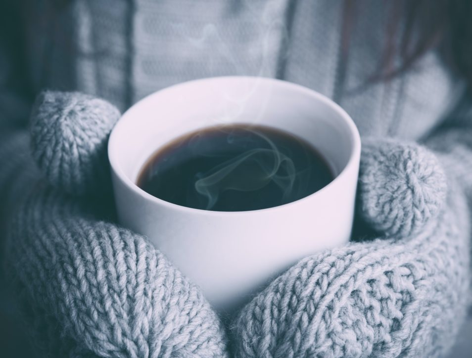 cup of coffee with two hands wearing mittens holding the cup