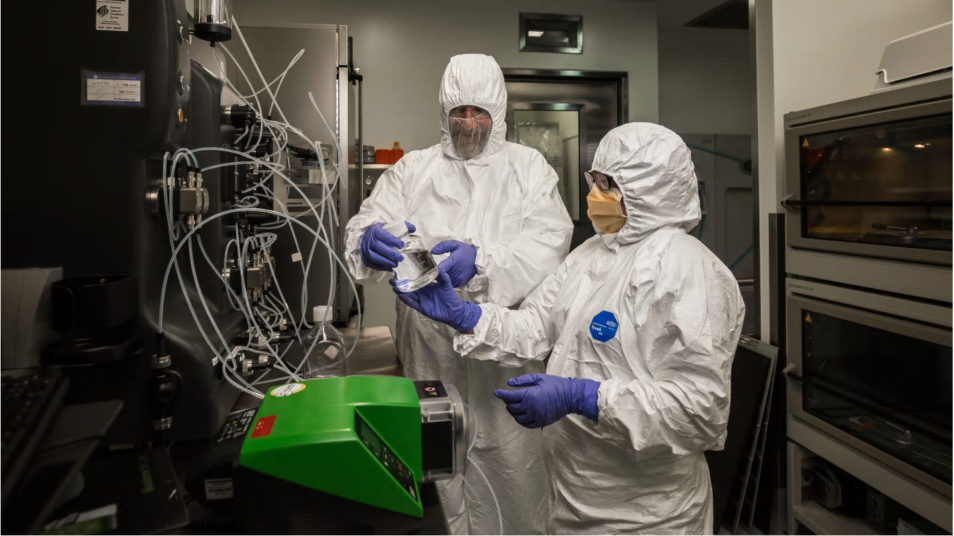 Two vaccine researchers in PPE gear at a machine looking at some results.