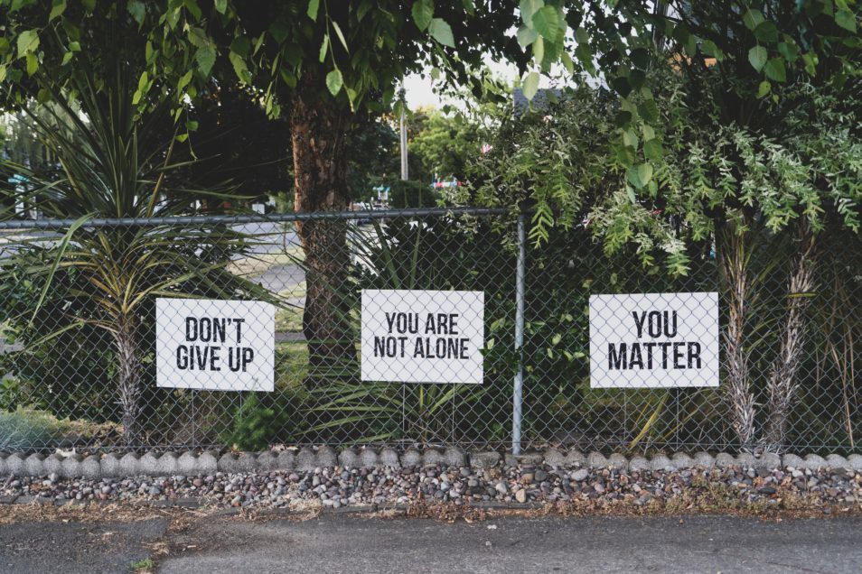 signs on wire fence with don't give up, you are not alone and you matter