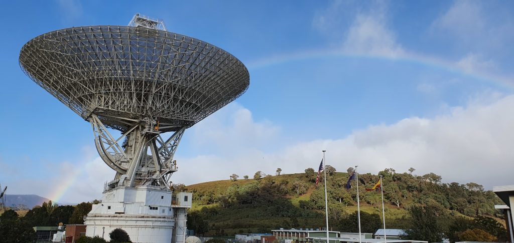 Deep Space Station 43 antenna dish with rainbow in the background