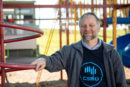 Dr Jurg Schutz holding onto some play equipment in a playground.