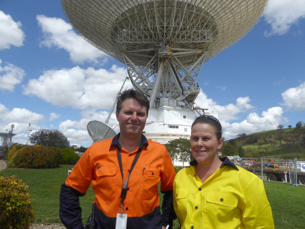 Two people in high-visibility tops standing in front of the Deep Space Station 43 antenna