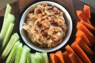 bowl of red lentil hommus surrounded by carrot and celery sticks