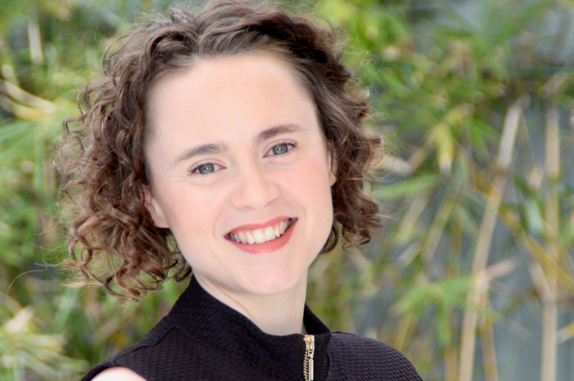 A woman with curly brown hair smiling at the camera