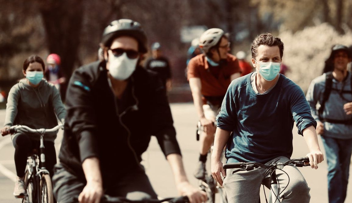 people in face masks riding bikes in town