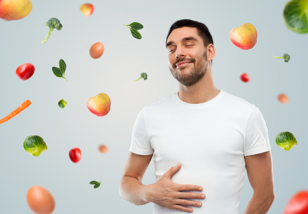 man with his hand on his gut and healthy fruit and veg around him