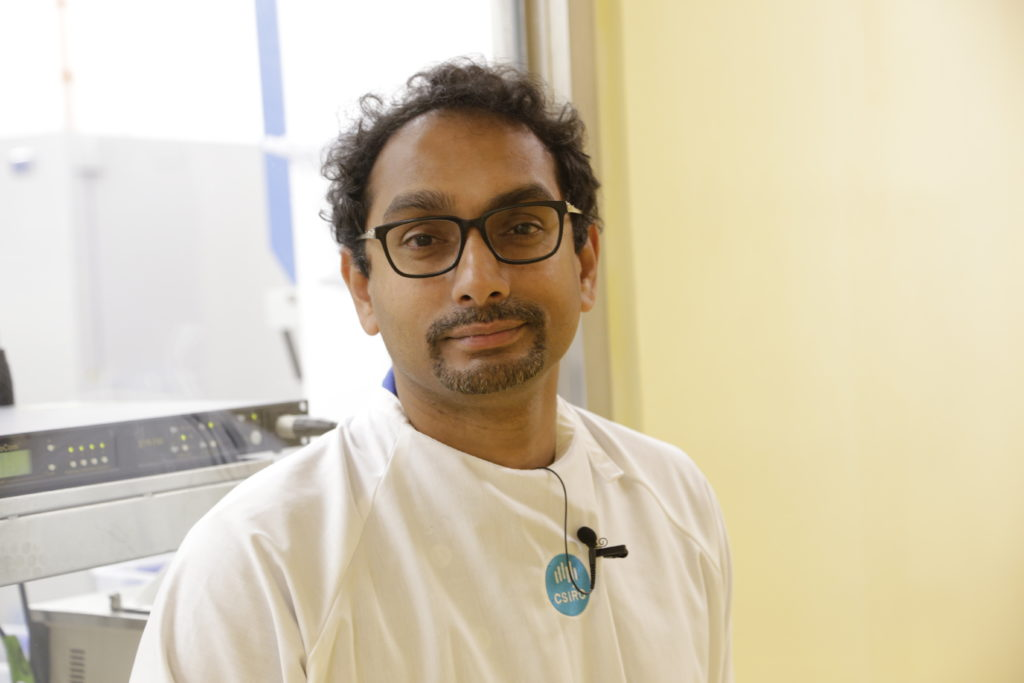 A man slightly smiling at the camera. He's wearing a white lab coat with a CSIRO logo.