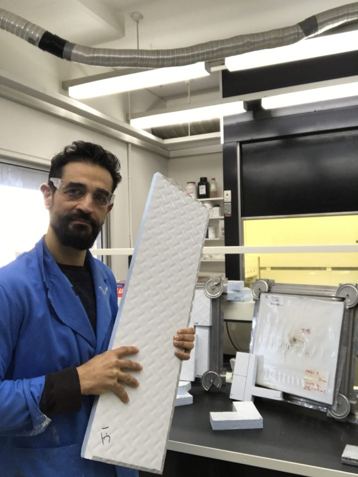 man holding fire-resistant panel facing camera in lab