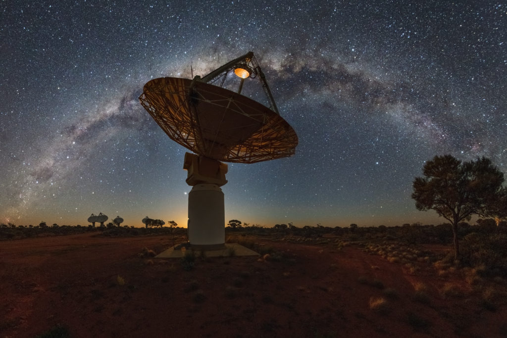 Dish-like white antenna with a starry sky above.