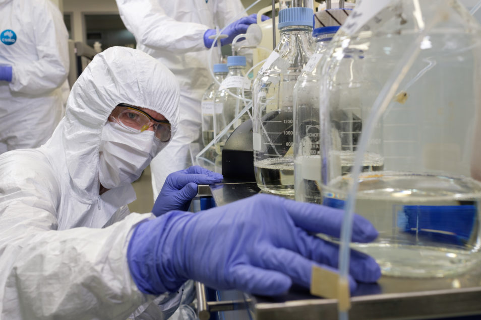 A researcher checks on their work in the lab while wearing full protective gear.