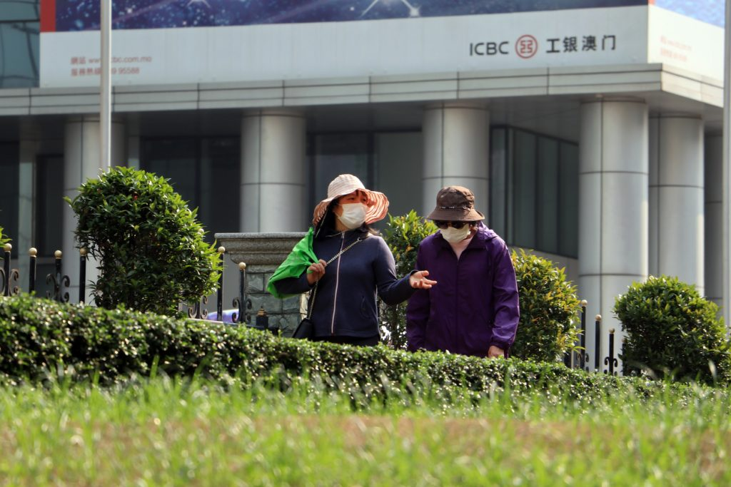 two people in face masks walking in a city by a green space