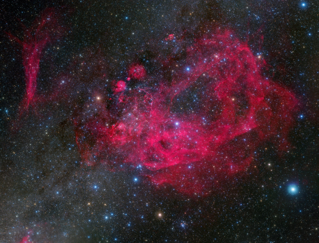 A hot pink galaxy against a black starry night. It's the Wide-Field Winner of the David Malin Awards.