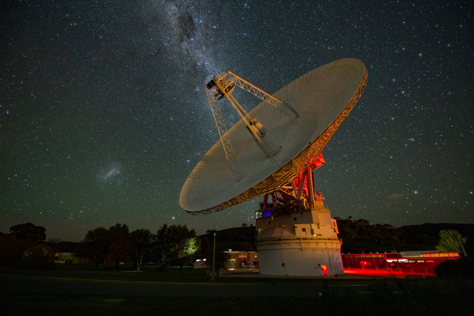 White dish-like antenna with a starry sky above