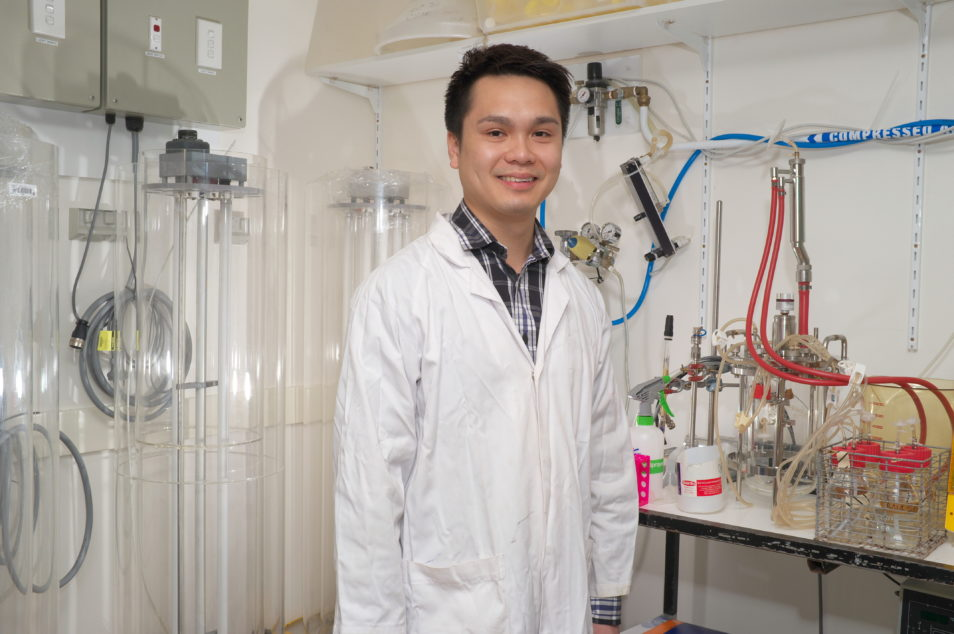 Kim Lee Chang in a lab wearing a white coat and smiling at the camera