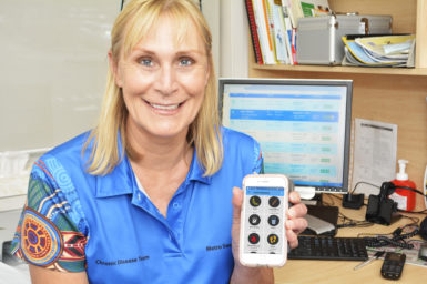 A woman smiling at the camera holding the M♡THer app. This tool will help manage gestational diabetes.
