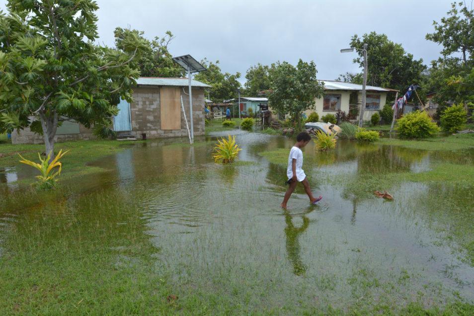Fijian girl walks over flooded land in Fiji
