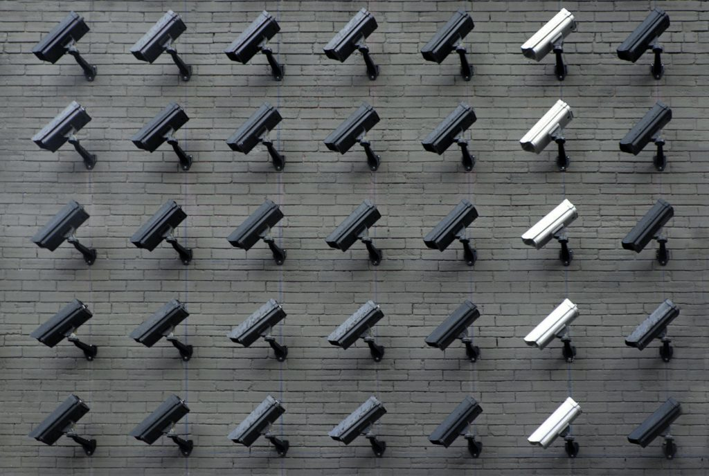 multiple rows of security cameras on a brick wall to illustarte cybersecurity attack