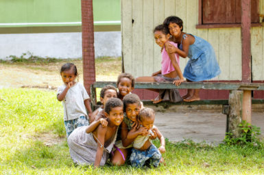 Unidentified children play in Lavena village. They're smiling at the camera.