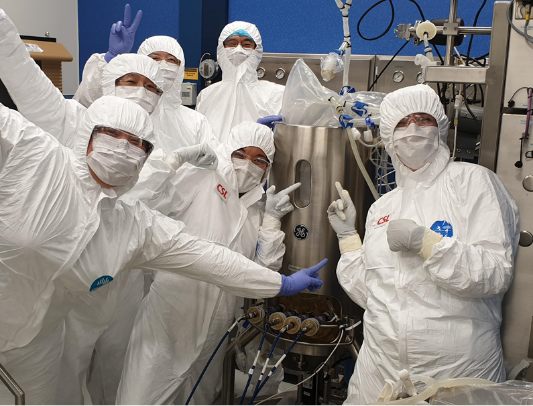 The team in full PPE and posing for the camera. They're working on the COVID-19 vaccine.