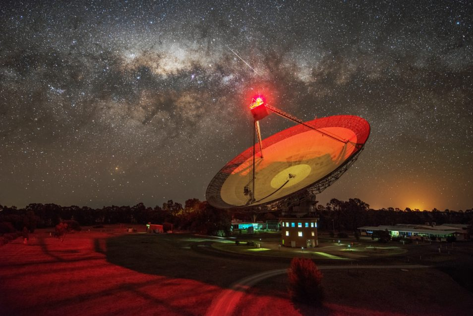 The Parkes radio telescope lit up with a red light, and a starry night sky above.