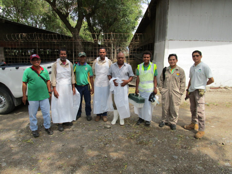 Eight people wearing disposable gowns to fight mosquito-borne diseases standing together near a white building.