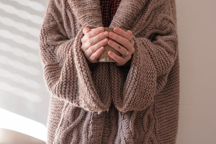 A woman wearing a wooly cardigan holding a coffee cup