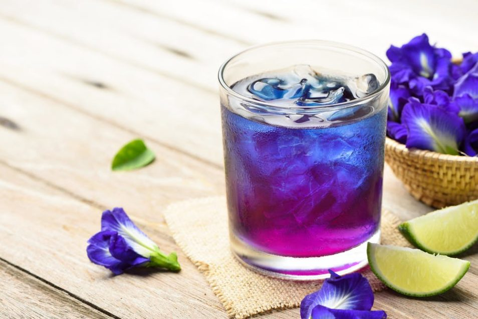 small glass with purple drink and ice on a table surrounded by small purple flowers