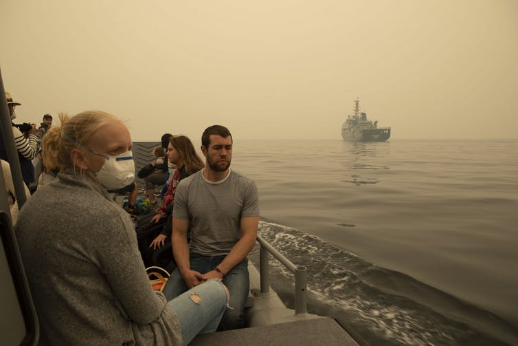 People sitting by the side of a lake with masks on. There's a ship in the background.