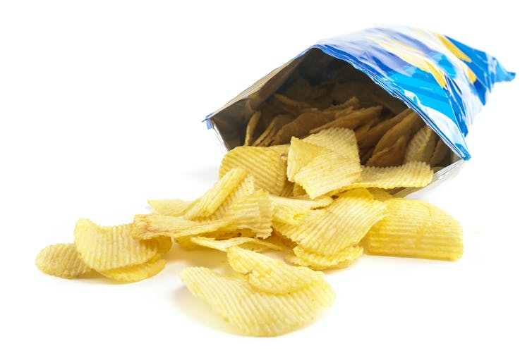 An open packet of chips with chips spilling out