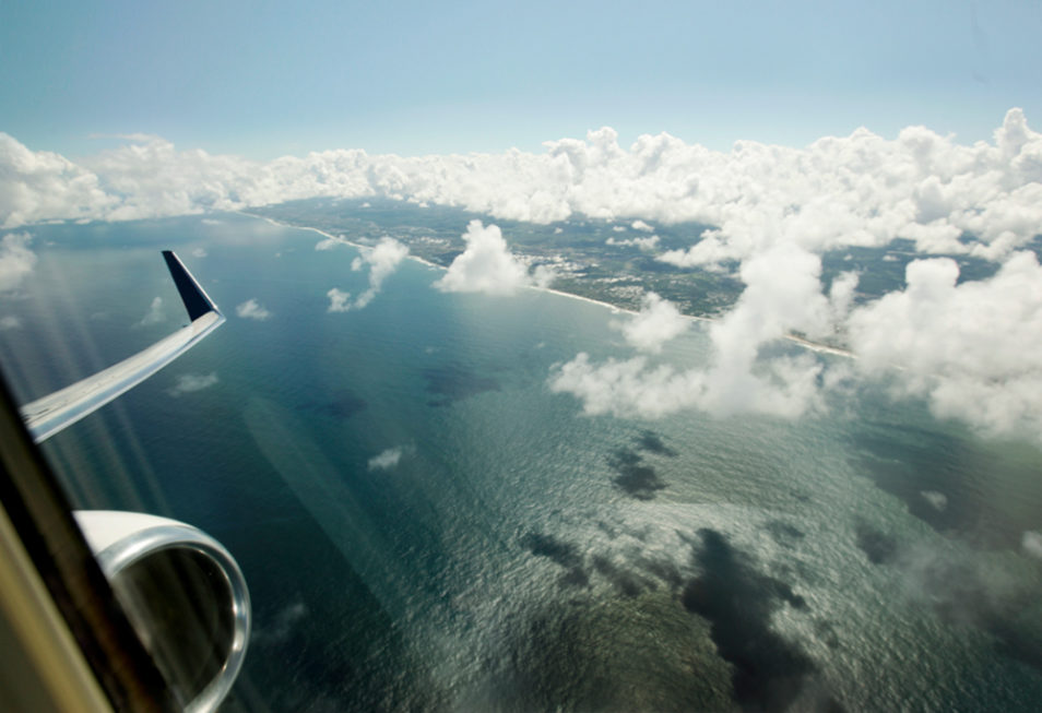 view from the airplane window during overflight at sea, in the city of Lauro de Freitas