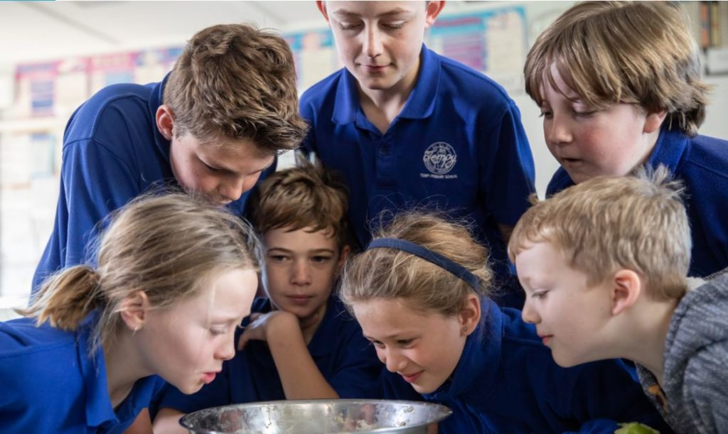 Children huddled around a bowl.