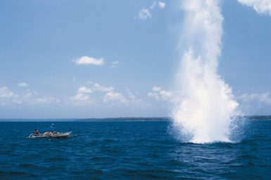 Fishing boat next to an explosive going off in the ocean, resulting in water going into the air