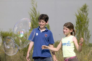 Exterior view of children playing with soap bubbles