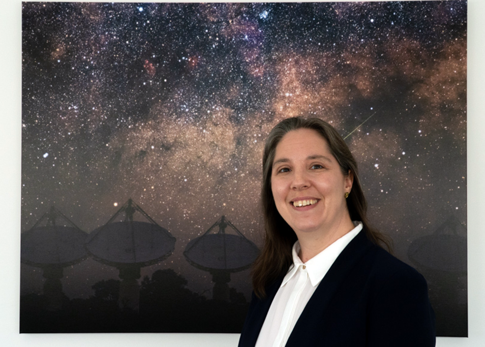 Dr Chenoa Tremblay stands in front of an image of a galaxy