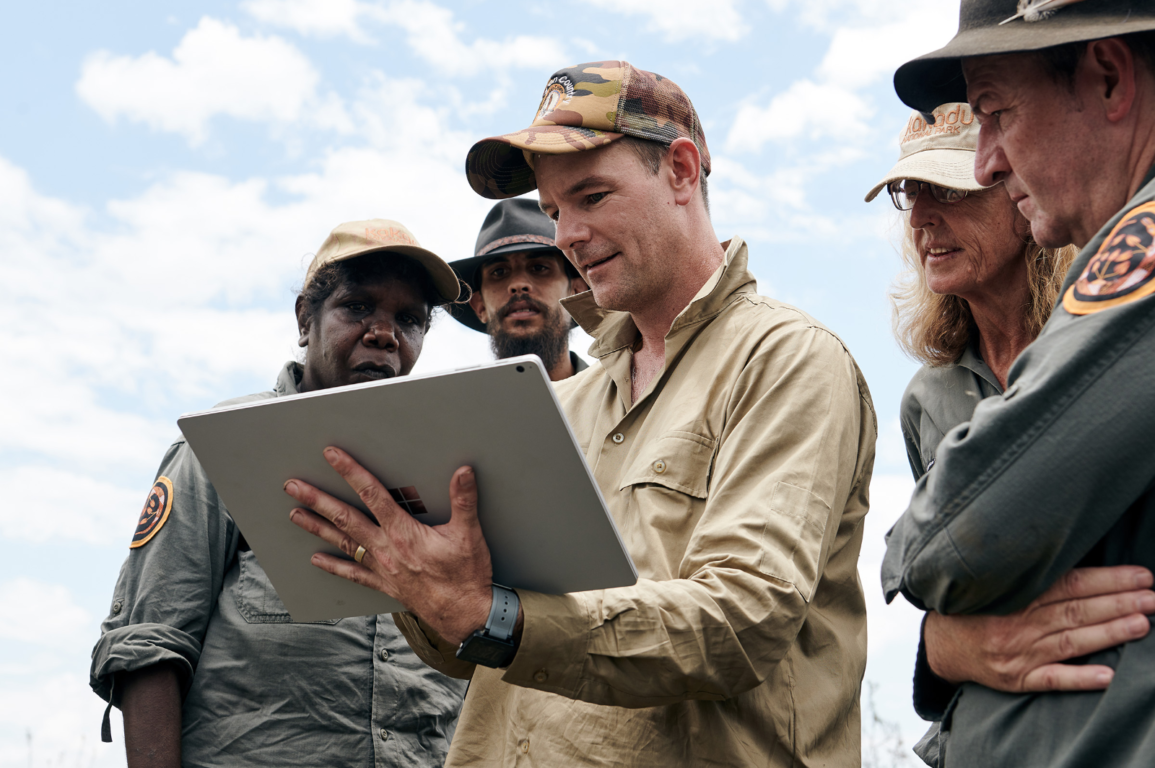 Dr Justin Perry looking at an Ipad with Indigenous rangers