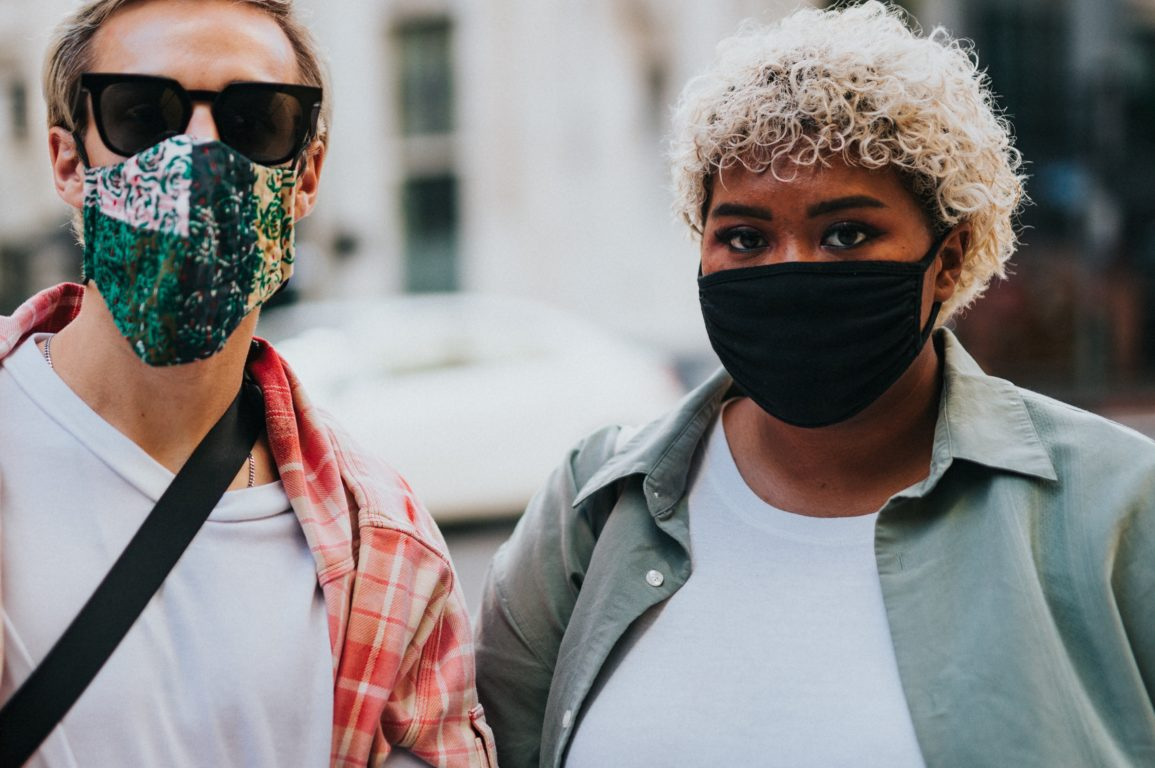 two people standing outside with masks on